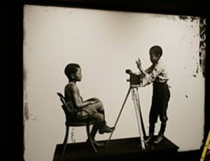 "In this Thursday, Aug. 27, 2015 photo, an 1891 portrait of Albert Jones and John Xiniwe, sitting for an unknown photographer for the London Stereoscopic Company, is displayed with other portraits made in studios across Britain in the 19th and early 20th century, in the show ""Black Chronicles II,"" as they are hung at the Ethelbert Cooper Gallery of African & African American Art in Cambridge, Mass. The show runs from Wednesday, Sept. 2, through Friday Dec. 11, 2015. (AP Photo/Stephan Savoia)"