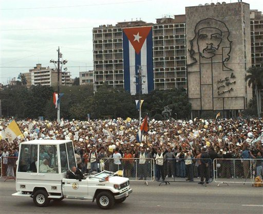 "In this Jan. 25, 1998 file photo, Pope John Paul II arrives to Plaza of the Revolution to celebrate Mass in Havana, Cuba, to celebrate Mass, where a  sculpture of Cuban revolutionary hero Ernesto ""Che"" Guevara covers the Interior Ministry building. (AP Photo/Joe Cavaretta, File)"