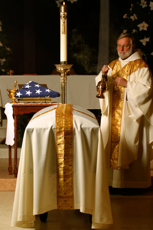 Fr. Richard Flaherty, OFM with a veteran's casket. (Courtesy of St. Anthony's Shrine)