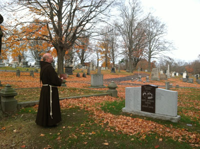 Fr. Barry Langley, OFM blesses a headstone at a Lazarus Ministry cemetery plot. (Courtesy of St. Anthony's Shrine)
