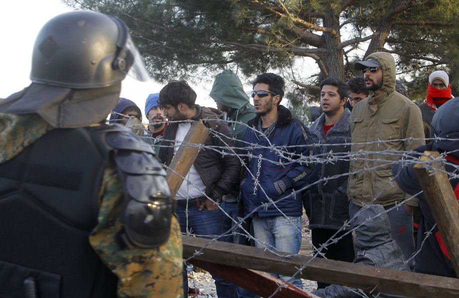 Macedonian riot police block migrants from entering into Macedonia after clashes with a violent group of migrants, on the border line between Macedonia and Greece, near southern Macedonian town of Gevgelija, Saturday, Nov. 28, 2015. (AP Photo/Boris Grdanoski)