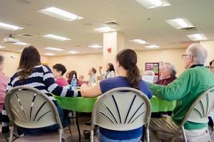 Seniors and Brandeis University volunteers hold hands during a reading of a poem. (Beth Treffeisen, NewBostonPost)