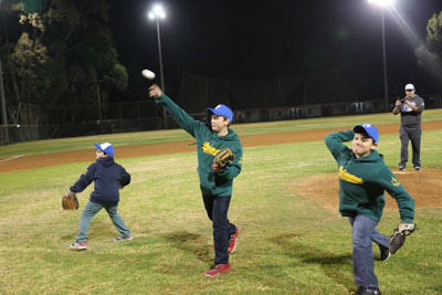 Ezra Schwartz's younger brothers—Avi, Elon, and Hillel—throw out the first pitch at an Israeli baseball game on Dec. 29. (Courtesy JNF)
