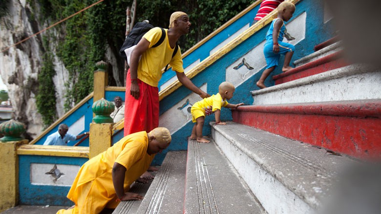 Suguna, far left, fulfills her Thaipusam pilgrimage by climbing the stairs leading to Murugan's shrine on her knees in Kuala Lumpur, Malaysia, on Jan. 24, 2016. She takes this journey together with her husband and two children. (Religion News Service photo by Alexandra Radu)