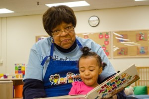 Foster Grandparent Bobbie Williams reads a book to Tiara, 22 months old, at the Head Start site in Dorchester. (New Boston Post, photo by Beth Treffeisen)