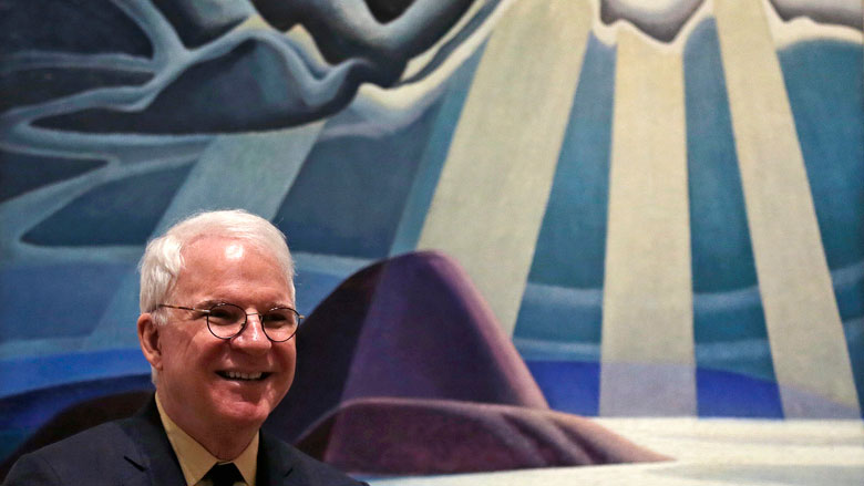 "Actor and comedian Steve Martin, who is guest curator of an exhibition at the Museum of Fine Arts devoted to Canadian modernist Lawren Harris, smiles, while seated in front of Harris's ""North Shore"" painting during a gathering at the museum in Boston, Friday, March 11, 2016. ""The Idea of North: The Paintings of Lawren Harris"" runs through June 12. (AP Photo/Charles Krupa)"