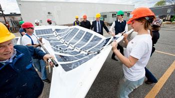 Derek Stein (green hard hat) and his team prepare construction materials. (Kristen Pelou/Techstyle Haus)