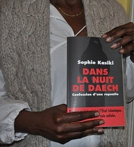 "Sophie Kasiki, one of the few Western women to have seen the Islamic State group's harsh ""caliphate"" in Syria and escaped, holds her book, recently published in France, that tells her story. The title, ""Dans la Nuit de Daech (In the Night of Daesh),"" uses the common French term for ISIS. The subtitle is ""Confession of a Repentant."" Photo taken on March 17, 2016. (Photo courtesy Religion News Service / Tom Heneghan)"