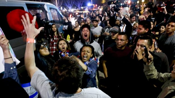 A Trump supporter clashes with protesters outside a rally in Costa Mesa, Calif., where the candidate spoke Thursday night. (AP Photo/Chris Carlson)