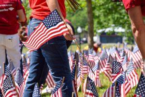 Volunteers help each other plant flags (New Boston Post photo by Beth Treffeisen)