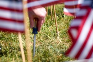 A volunteer stands out in the heat using a screw driver to dig hole in order to place an American flag (New Boston Post photo by Beth Treffeisen)