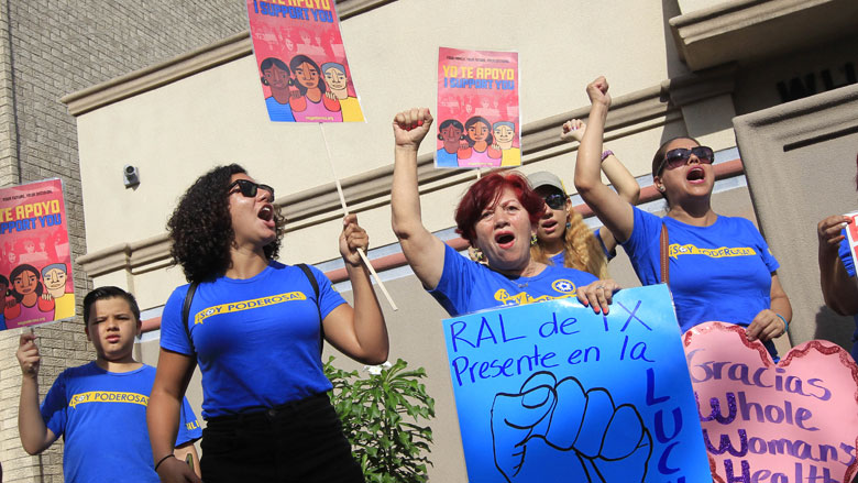 Lucy Ceballos, center, and Isabella Soto, left, members of the National Institute for Reproductive Health, celebrate the U.S. Supreme Court ruling against Texas' abortion restrictions in front of Whole Woman's Health Monday, June 27, 2016, in McAllen, Texas. (Nathan Lambrecht/The Monitor via AP)