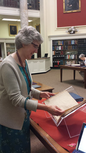 Lauren Hewes, the Andrew W. Mellon Curator of Graphic Arts, with rare broadsides. (NewBostonPost photo by Mary McCleary)
