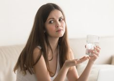 Doubtful worried woman holding pill, glass of water at home