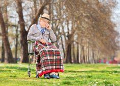 Grumpy old man sitting in a wheelchair in park