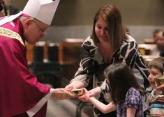 Archbishop Charles Chaput Photo — Receiving Gifts From Children During Mass — Archdiocese of Philadephia Photo — Saved Tuesday 10-2-2018