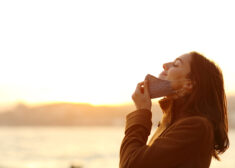 Woman taking off mask to breath fresh air on the beach
